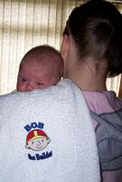 Picture of a baby and an embroidered Bob the Builder burp cloth